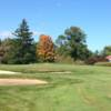 A view of a green protected by bunkers at Hop Meadow Country Club