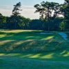 A view of a green protected by bunkers at The Country Club