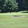 A view of a green protected by a bunker at Millwood Farms Golf Course