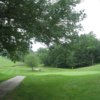 A view of a green with a narrow path on the left side at Berlin Country Club