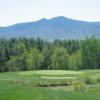 A view of a green with mountains in the distance at Waumbek Country Club